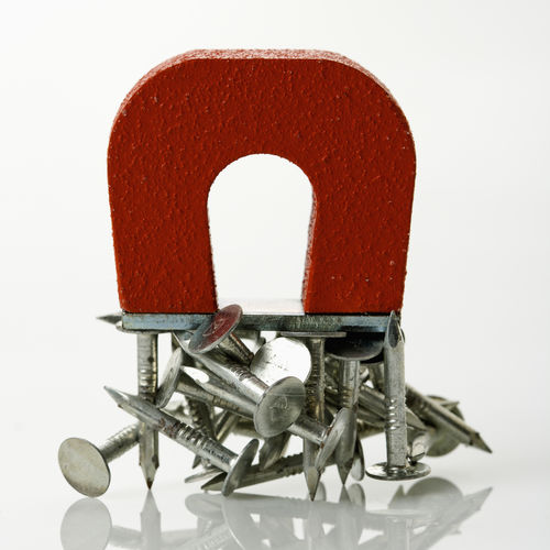 Red Magnet Holding Metal Nails On White Background