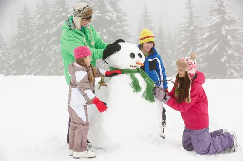 Group Of Children Building Snowman On Ski Holiday In Mountains