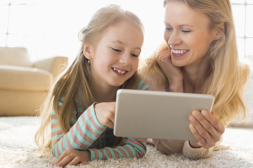 Happy Mother And Daughter Using Digital Tablet On Floor At Home