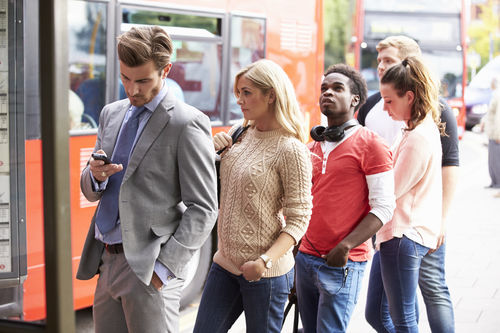 Queue Of People Waiting At Bus Stop